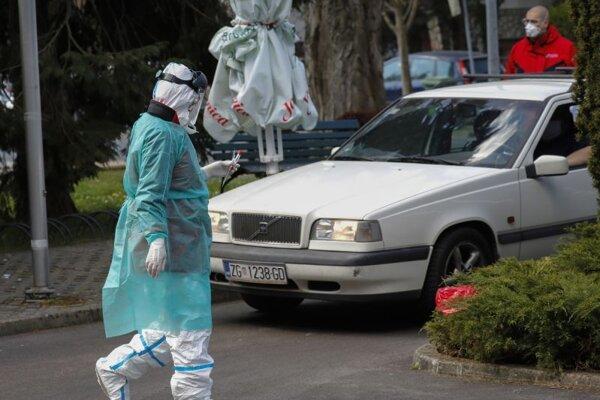 Šofér v aute čaká na odbernom mieste, ktoré slúži na testovanie nového koronavírusu u ľudí priamo z okna auta v Záhrebe.