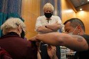 Britský premiér Boris Johnson pri návšteve vakcinačného centra v Londýne pozoruje, ako posilňovaciu dávku dostáva 88-ročná Nitza Sarnerová.
