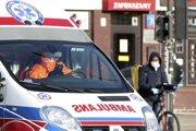 Sanitka prechádza okolo cyklistu s ochranným rúškom na tvári vo Varšave.