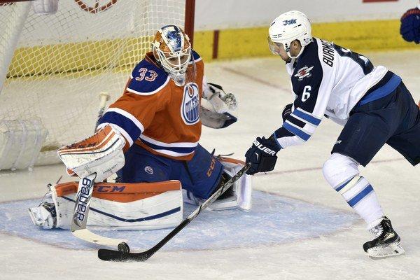 """Gólman Edmontonu Cam Talbot zastavuje pokus Alexandra Burmistrova z Winnipegu Jets. Domáci """"olejári"""" vyhrali na domácom ľade aj s pomocou Andreja Sekeru 3:1."""