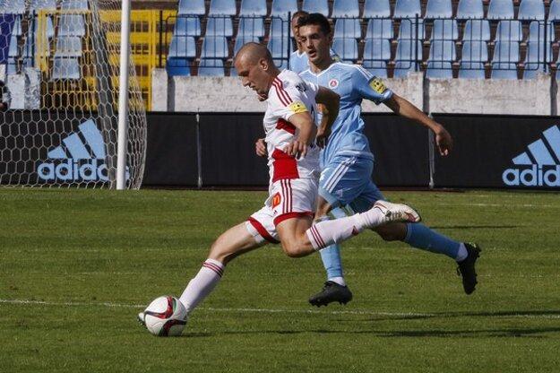 Na snímke z posledného ligového súboja sa hráč Trenčína Milan Rundič (vľavo) snaží odcentrovať spoza Vukana Savičeviča zo Slovana.