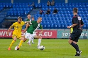 Hráč Skalice Roman Konečný (s číslom 3) sa snaží uvoľniť s loptou, zozadu sa ho pokúša zastaviť Michal Hamuľák.