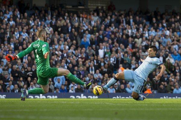 Brankár Manchesteru David de Gea sa snaží zakročiť proti šanci Sergia Agüera. V súčasnosti patrí medzi najväčšie opory Manchesteru United.