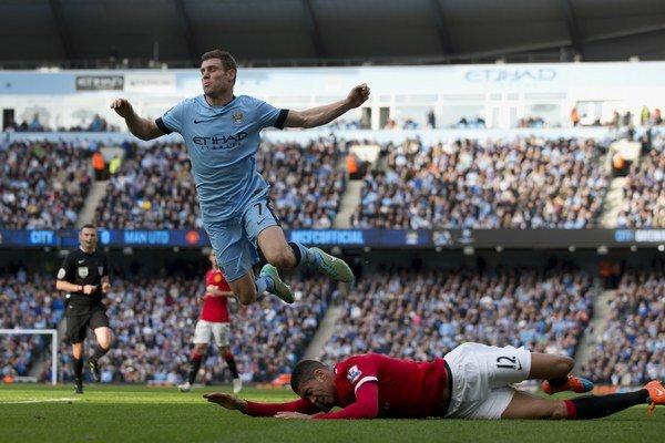 Na snímke dole  hráč United Chris Smalling fauluje hráča City Jamesa Milnera (hore), za zákrok dostal druhú žltú a vzápätí červenú kartu.