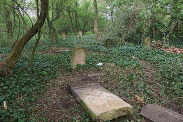 Poškodený náhrobný kameň.