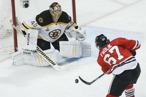 Michael Frolík strieľa na Fína Ruska v piatom zápase finále NHL, ktorý jeho Chicago vyhralo 3:1.