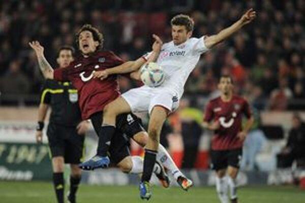 Emanuel Pogatetz v drese Hannoveru (vľavo) a hráč Bayernu Thomas Mueller.