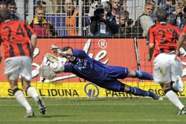 Brankár Frankfurtu Ralf Faehrmann chytá penaltu v zápase s Dortmundom.