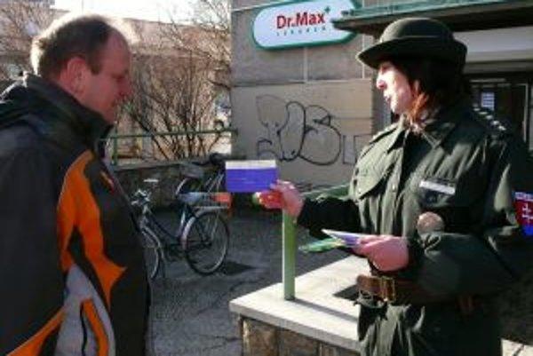 Policajná preventistka upozorňuje chodca na pravidlá cestnej premávky.