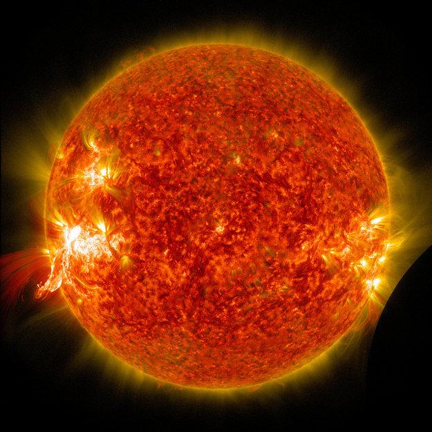 Ďalšiu solárnu erupciu môžeme vidieť ako jasný záblesk v ľavej časti fotografie. V pravo dole je viditeľný aj tieň Mesiaca.
