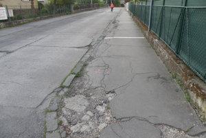 Na Krátkej ulici v Prievidzi je poškodený chodník. Parkujú na ňom autá.