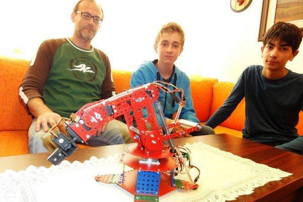 Zľava M. Lampert, M. Pintér a R. Baláž s modelom robotickej ruky.