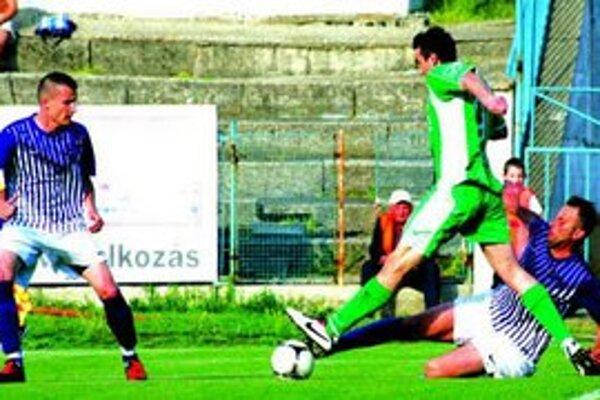 Ilustračné foto zo zápasu KFC - Šúrovce z pred dvoch kôl. Na nej Komárňania Szórád (na zemi) v súboji s hráčom Šúroviec, prizerá sa Podlucký.