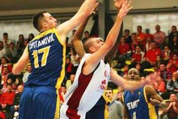 Komárňan Šoška (v bielom) sa presadil medzi troma brániacimi hráčmi.