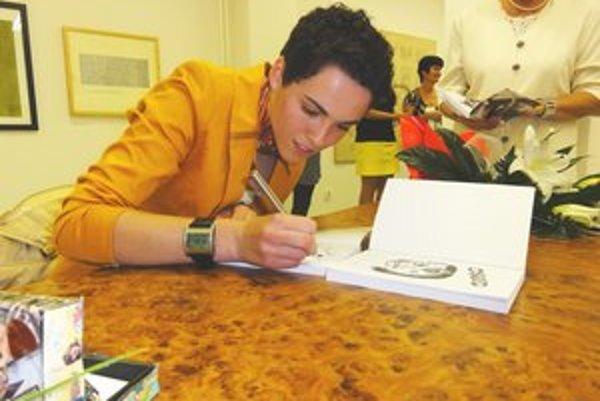 Mladá autorka podpisuje svoje knihy.