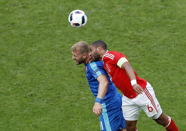 Adam Nemec (vľavo) bojuje v hlavičkovom súboji o loptu s kapitánom Walesu Ashleym Williamsom.