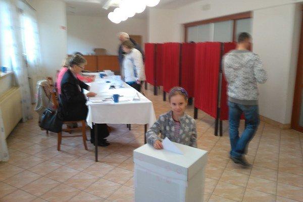"""Budúca volička na """"zácviku"""". Vložiť hlasovací lístok do urny prišla s mamkou 6–ročná Janka Drochytková."""