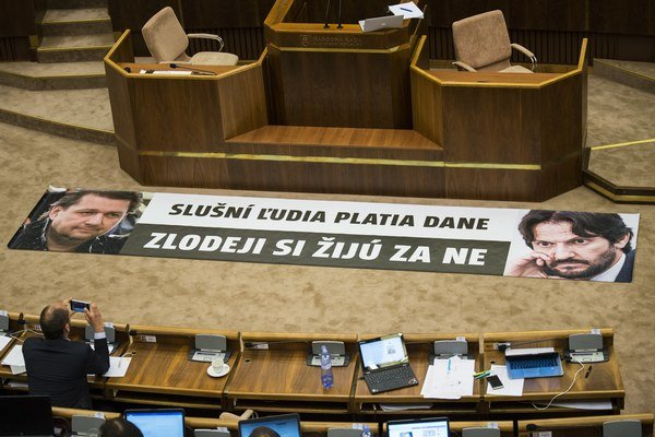 Na snímke transparent s nápisom Slušní ľudia platia dane, zlodeji si žijú za ne, ktorý rozložil predseda strany OĽaNO-Nova Igor Matovič pred rečníckym pultom v rokovacej sále parlamentu.
