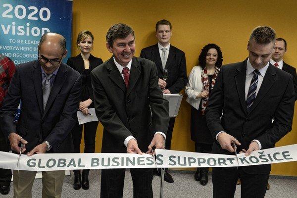Zľava: Moises Mouta z GBS, riaditeľ GBS Raul Moreira a námestník košického primátora Martin Petruško strihajú pásku počas slávnostného otvorenia podporného centra GBS.