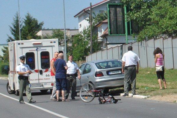 Bicykel na ceste. Mladú ženu ošetrovali v sanitke.