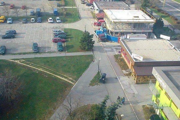Vedľa poloprázdneho parkoviska. Autá stoja na chodníkoch.