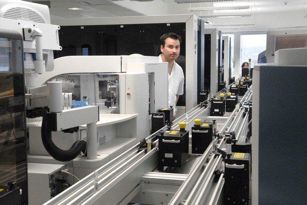 Automatický pás so vzorkami. Skúmavky si z nich berie robotická ruka.