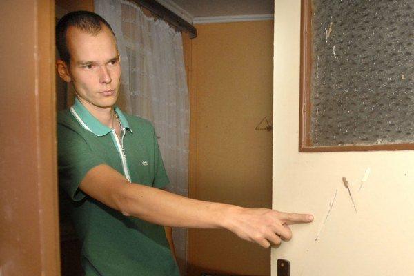 Napadnutý Tomáš ukazuje, kde sused sekal, on sa zatiaľ skrýval za týmito dverami.