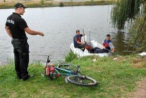 Miesto, kde nechal veci. Policajt naviguje hasičov k brehu.