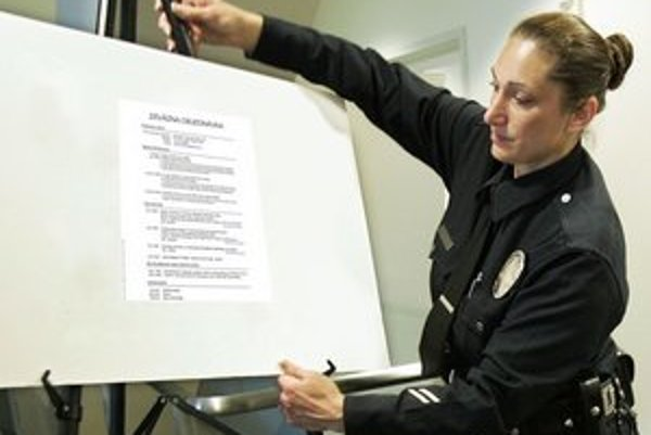Šéfka protikorupčného oddelenia ukazuje policajný dôkaz.
