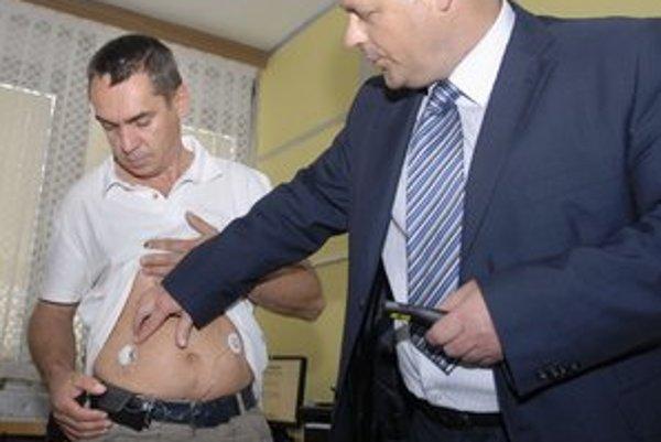Pacient. Senzor má zavedený do podkožia, pumpu na opasku a bruchu. Vedľa Miroslav Paľko.