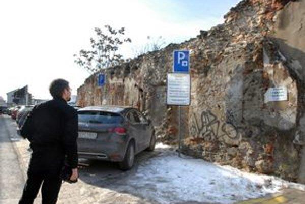 """Na múre """"Pozor, padajú kamene"""". Na značke """"Platené parkovisko – hodina za 1 euro"""""""