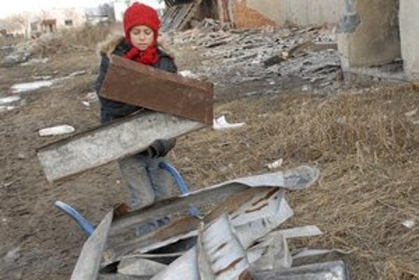 Strhnutá strecha. Deti ju odnášajú na fúrikoch.