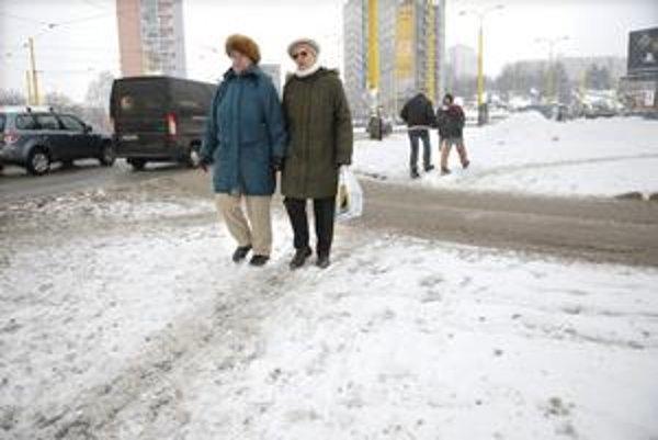 Dôchodkyne na prechádzke. Neodprataná topiaca sa vrstva snehu ich včera poriadne nahnevala.