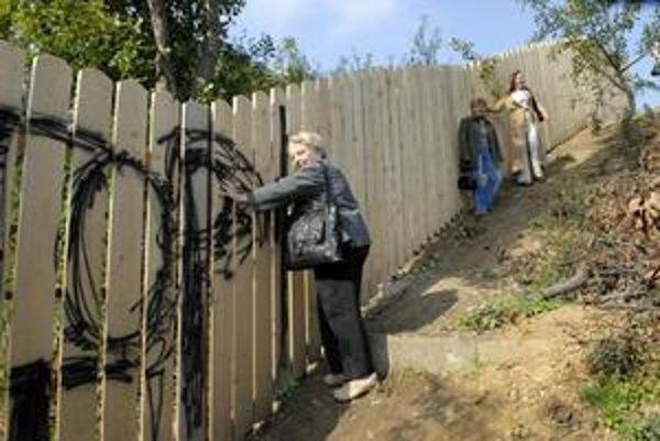 Ohradený pozemok. Kvôli plotu musia obyvatelia použiť obchádzku. Trvá im o 15 minút dlhšie.