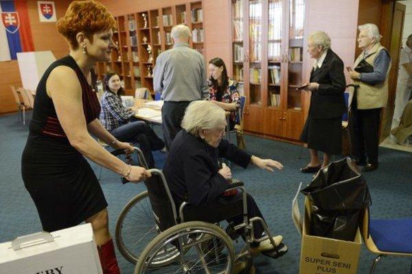 Na snímke vpravo 101-ročná Anna Ňachajová opúšťa volebnú miestnosť. S vozíkom ju sprevádza vedúca sestra Alena Ivančová.