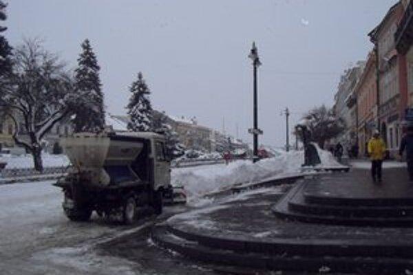 Centrum mesta. Popri chodníkoch vznikajú snehové steny.