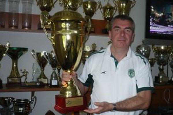 Miloslav Chmeliar. Za ním je časť zbierky najcennejších trofejí.