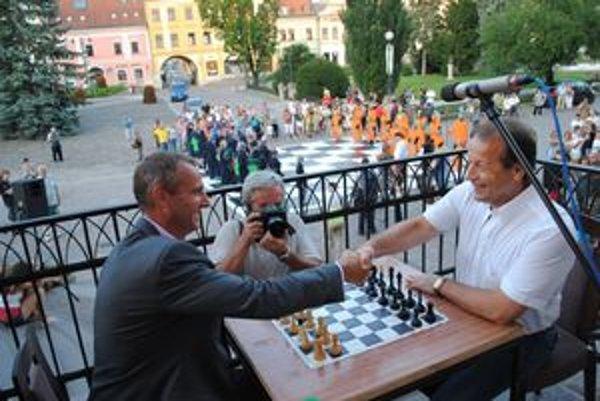 Rivali. Primátorov spojil šach, dole na ich pokyny čakali bojovníci.