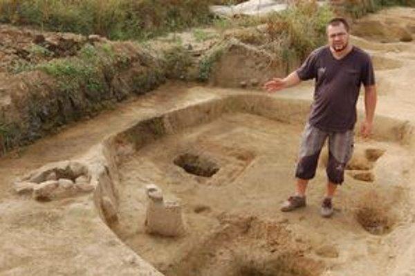 Archeológ Comisso v jednej zo zahĺbených chát s ohniskom.