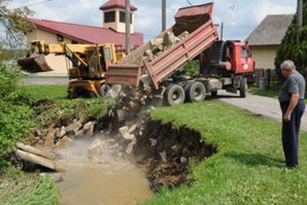 Mechanizmy dnes od rána pracujú v Hlinnom na odstraňovaní následkov povodne a pri spevňovaní koryta potoka.