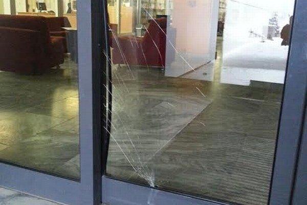 Rozbité sklo na dverách.