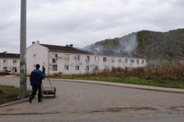 Mestské bytovky v osade. Nájomníci na vozíkoch privážajú všetko, čo sa dá spáliť.