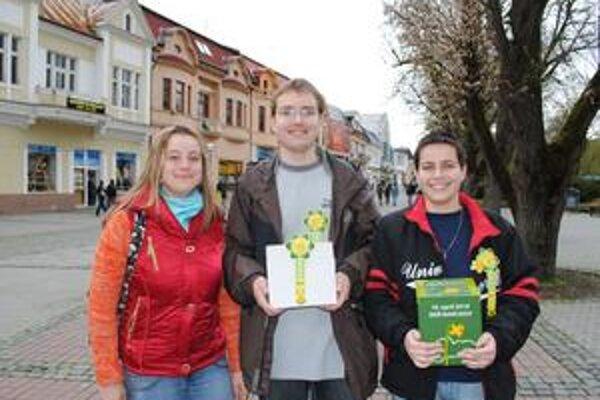 Dobrovoľníci: Mirka Hodorová (vľavo), Vlado Kendereš a Petra Macková, študenti SPČHP v Humennom ponúkali v piatok v uliciach mesta Humenčanom symbol boja proti rakovine - žltý narcis.
