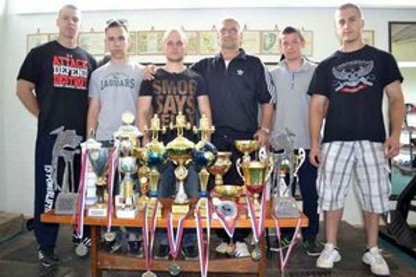Čenovia klubu ŠK Zemplín Michalovce silový trojboj. Pätica mladíkov so svojím trénerom Ladislavom Lechanom. V popredí víťazné trofeje aj medaily z rôznych súťaží.