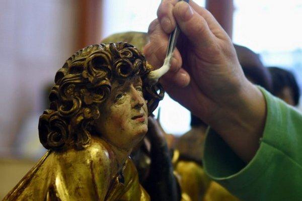Reštaurátorka čistí od nánosov prachu jednu zo sôch z oltára Štyroch svätých Jánov z Kostola svätého Jakuba v Levoči.