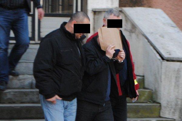 Útočníka so zakrytou tvárou odvádzajú z budovy polície v Spišskej Novej Vsi.