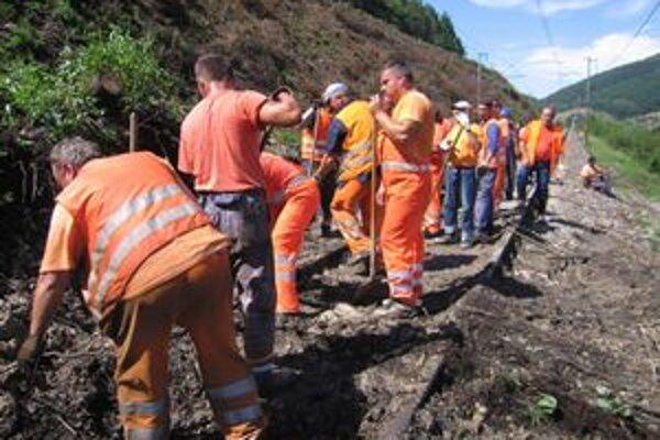 Pracovníci železníc odstraňujú zosuv na trati.