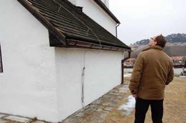 Správca kostola. Díva sa na poškodenú strechu sakristie.