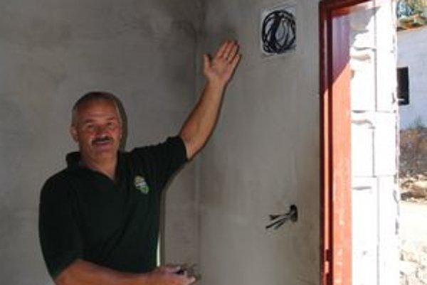 Ukradnuté káble. Anton Petruľák ukazuje zvyšky káblov, ktoré ostali v stene.