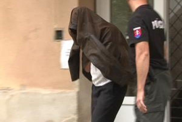 Predpokladaný páchateľ. Tvár si zakryl odevom.
